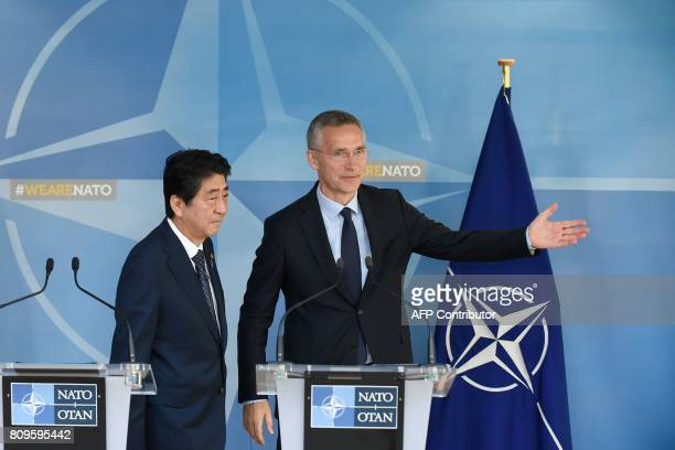 NATO chief Jens Stoltenberg gestures next to Japanese Prime Minister Shinzo Abe at the end of a press conference at the NATO headquarters in Brussels...