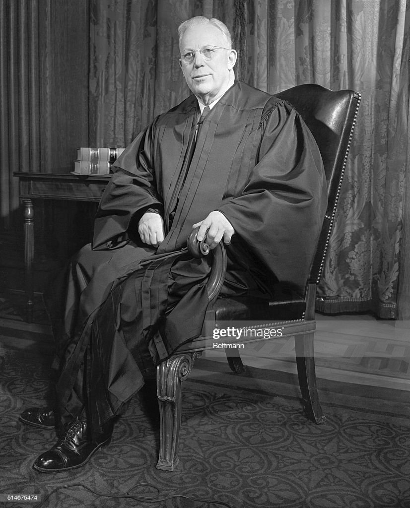 Chief Justice Earl Warren poses for a portrait while seated wearing his robes Warren the 14th chief justice of the United States presided between...