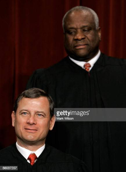 Chief Justice John G Roberts Justice Clarence Thomas pose for photographers at the US Supreme Court October 31 2005 in Washington DC Earlier in the...