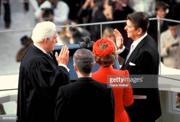 Chief Justice Warren Burger swearing in Ronald Reagan as Mark Hatfield Reagan's wife Nancy look on during US Presidential inauguration