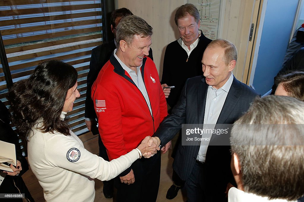 Chief Marketing Officer Lisa Baird (L) shakes hands with Russian President Vladimir Putin (R) as Chief executive officer of the U.S. Olympic Committee Scott Blackmun (red) and U.S. Olympic Committee chairman Larry Probst look on at the USA House in the Olympic Village on February 14, 2014 in Sochi, Russia.