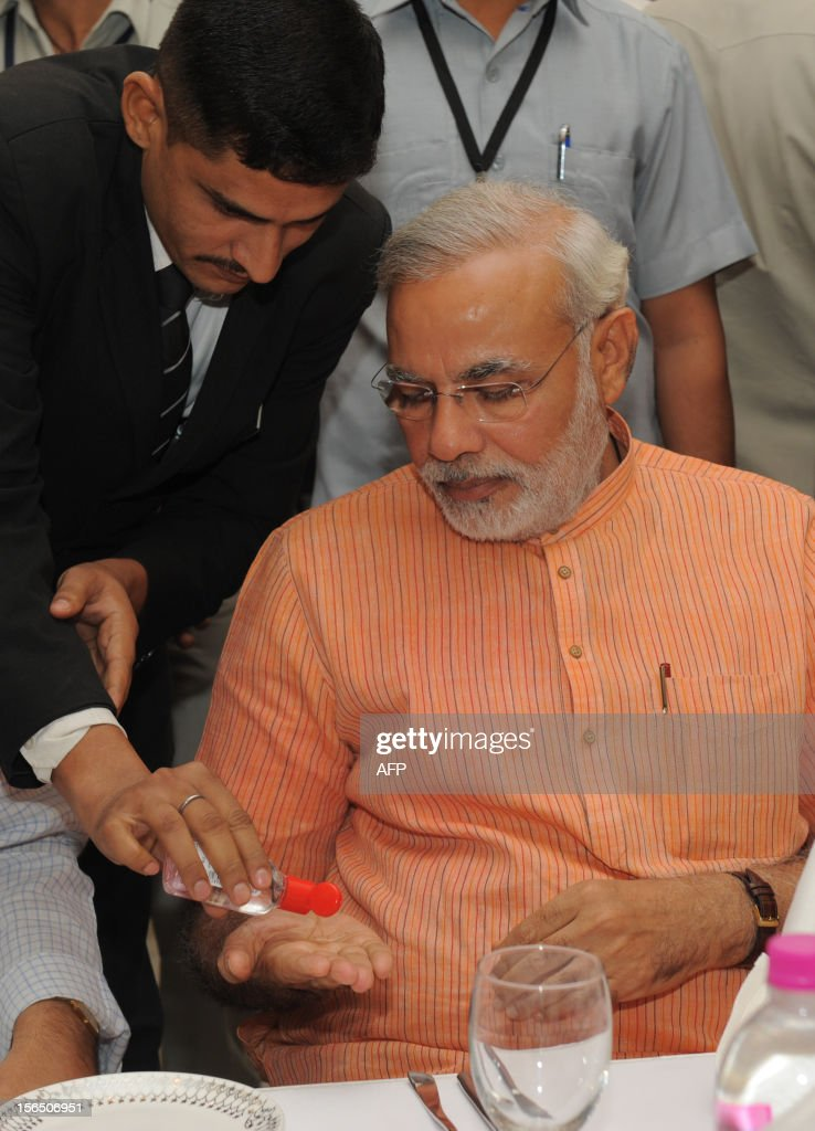 Chief Minister of India's western state of Gujarat, Narendra Modi (R) is given sanitizer by a hotel staff member in Ahmedabad on November 16, 2012. India's Bharatiya Janata Party (BJP) announced that it would use three-dimensional (3-D) audio-visual technology in its campaign for State Assembly polls in Gujarat which fall in December. The high-tech campaign which will start on November 18, would show Modi visibly addressing public meetings at Ahmedabad, Vadodara, Rajkot and Surat without his real-time presence. AFP PHOTO / Sam PANTHAKY