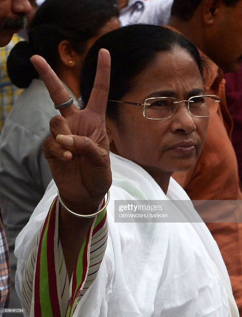 Chief minister of the eastern Indian state of West Bengal and Leader of the ruling Trinamool Congress(TMC) Mamata Banerjee,flashes a 'victory sign' after casting her vote for state assembly elections at a polling station in Kolkata on April 30, 2016. State assembly elections in West Bengal are taking place from April 4 to May 5. / AFP / Dibyangshu SARKAR
