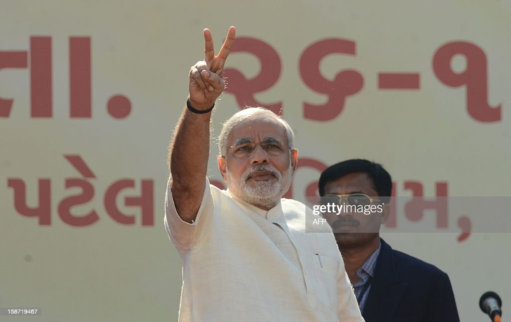 Chief Minister of the western Indian state of Gujarat Narendra Modi flashes a victory sign to supporters as he participates in a swearing in ceremony at The Sardar Patel Navrangpura Stadium in Ahmedabad on December 26, 2012. Modi who won a landslide victory in recent state assembly polls, was administered the oath of office and secrecy by Gujarat Governor Kamla Beniwal at a ceremony which was attended by many senior BJP leaders. AFP PHOTO/Sam PANTHAKY