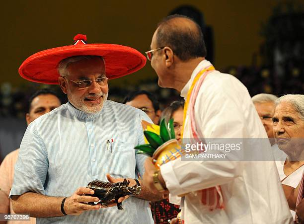 Chief Minister of the western Indian state of Gujarat Narendra Modi wears a hat from the northeastern state of Assam as he interacts with guests...