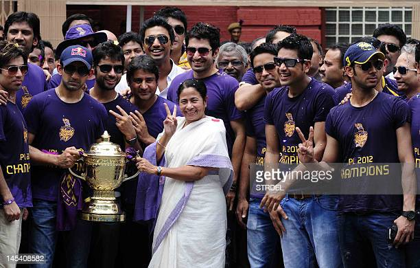 Chief minister of West Bengal Mamata Banerjee holds the IPL Twenty20 champion's trophy with Kolkata Knight Riders captain Gautam Gambhir as teammates...