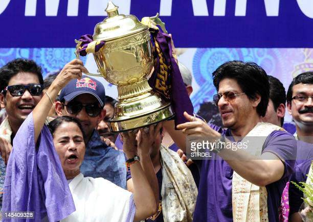 Chief minister of West Bengal Mamata Banerjee holds the IPL Twenty20 champion's trophy with Kolkata Knight Riders owner Shah Rukh Khan during...