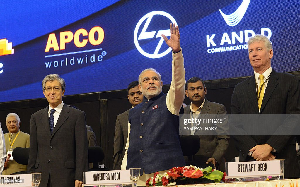 Chief Minister of Western India's Gujarat state, Narendra Modi (C) waves to supporters as Japanese Envoy, Takeshi Yagi (L) and Canadian High Commissioner, Stewart Beck (R) looks during the launch of Vibrant Gujarat 2013 6th Global Summit at Mahatma Mandir in Gandhinagar, some 30 kms from Ahmedabad on January 11, 2013. The summit is being attended by national and international corporations in large numbers. AFP PHOTO / Sam PANTHAKY