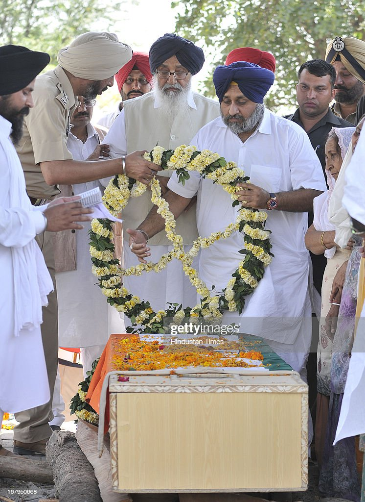 Chief Minister Punjab Parkash Singh Badal along with Deputy Chief Minister Punjab Sukhbir Singh Badal as laying the wreath on the pyre of Sarabjit Singh during his cremation ceremony at his native village Bikhiwind on May 3, 2013 about 40 Kms from Amritsar, India. Sarabjit Singh, an Indian prisoner in Pakistan who died after being brutally assaulted in a Pakistani jail, was cremated in his native village with full state honours.