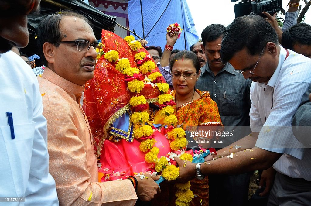 Chief minister Shivraj Singh Chouhan and his wife Sadhna Singh carrying a Ganesha idol to their official residence at Shyamla hills from Mata Mandir Market on the occasion of Ganesha Chathurthi festival on August 29, 2014 in Bhopal, India. The ten-day long Ganesh festival kicked off with zeal and fervour across Maharashtra with lakhs of devotees queueing up outside temples to offer prayers to the elephant-headed deity. The district administration has put a ban of use of idols made from plaster of Paris with a view to prevent pollution of rivers and ponds.