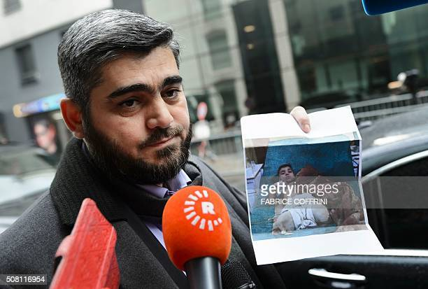 TOPSHOT Chief negotiator for the main Syrian opposition body Army of Islam rebel group's Mohammed Alloush holds a picture showing a wounded child...