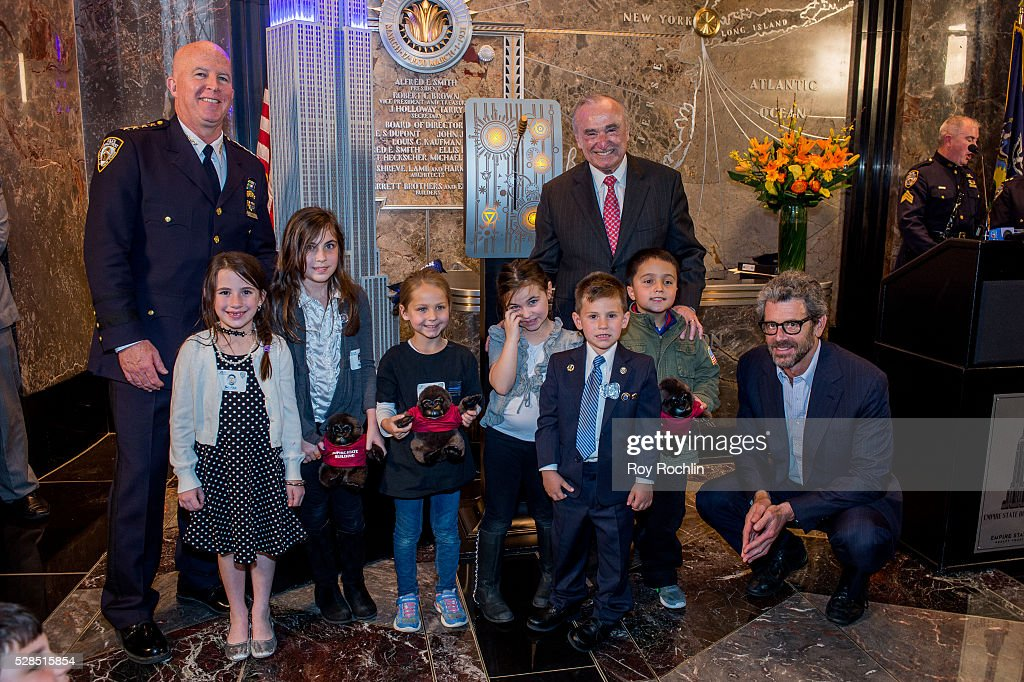 Chief of department James P. O'Neill and NYC Police Commissioner William Bratton pose with children of fallen police officers as Bratton lights the Empire State Building in honor of Police Memorial Week on May 5, 2016 in New York City.