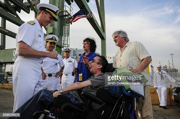 Chief of Naval Operations CNO Admiral Jonathan Greenert presents his coin to a military supporter at the USO New York City Fleet Week block party New...