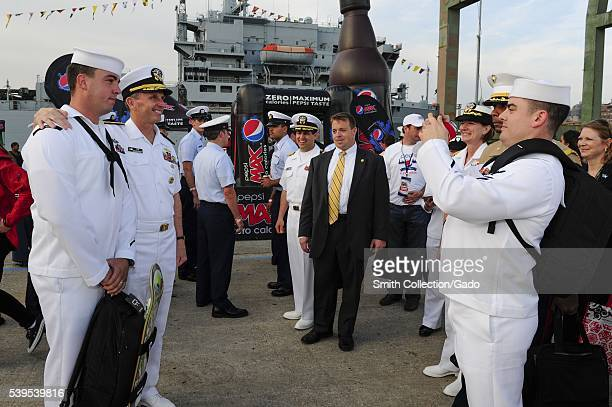 Chief of Naval Operations CNO Admiral Jonathan Greenert stops to take a photo with a Sailor at the USO New York City Fleet Week block party New York...