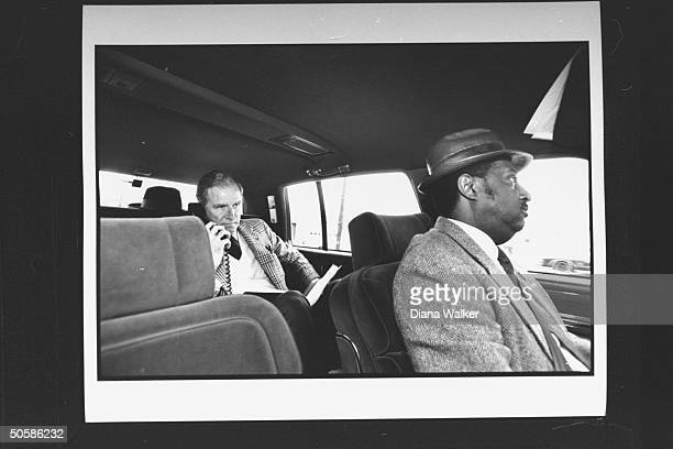 US Chief of Protocol Joseph Reed behind his black chauffeur in back seat of his private car making a telephone call