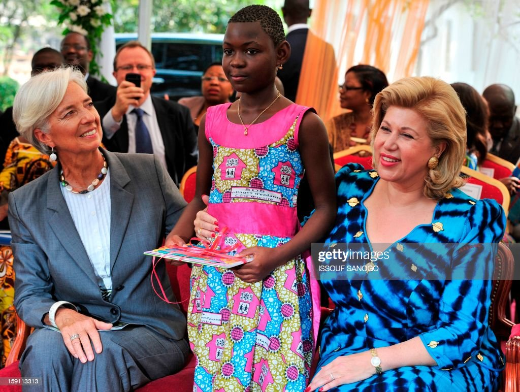 chief of the International Monetary Fund, Christine Lagarde (L) and Ivory Coast first lady Dominique Ouattara (R) pose with a girl as they visit an orphanage in Abobo, suburb of Abidjan on January 8, 2013. Lagarde, called for 'a second Ivorian economic miracle' during a visit to Abidjan as part of an African tour. AFP PHOTO / ISSOUF SANOGO