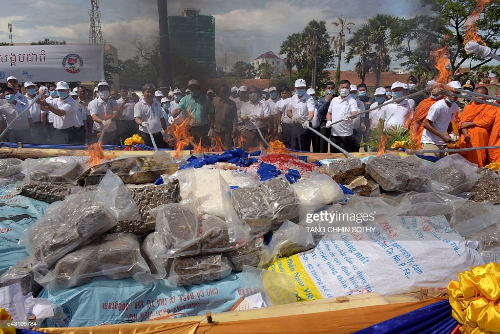 Chief of the National Authority for Combating Drugs Ke Kim Yan (C, in green shirt) and officials burn drugs during a destruction ceremony to mark the UN's 'International Day against Drug Abuse and Illicit Trafficking' in Phnom Penh on June 26, 2016. Cambodian authorities burned nearly 2 tons of seized drugs during the event. / AFP / TANG