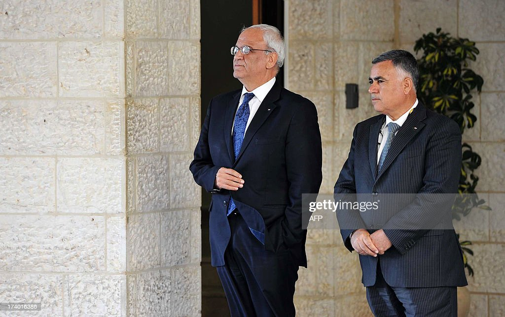 Chief Palesinian negotiator Saeeb Erakat (L) and one of his deputy wait for US Secretary of State John Kerry before his meeting with Palestinian President Mahmud Abbas on July 19, 2013 at the Mukataa compound, in the West Bank city of Ramallah. Kerry flew by helicopter to the West Bank from Jordan to meet Abbas as he battled to salvage his Middle East peace bid. AFP PHOTO/POOL / FADI AROURI