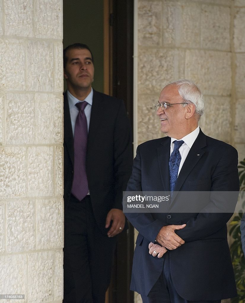 Chief Palesinian negotiator Saeeb Erakat (R) smiles as US Secretary of State John Kerry arrives on July 19, 2013 at the Mukataa to meet with Palestinian President Mahmud Abbas in the West Bank city of Ramallah. AFP PHOTO/Mandel NGAN