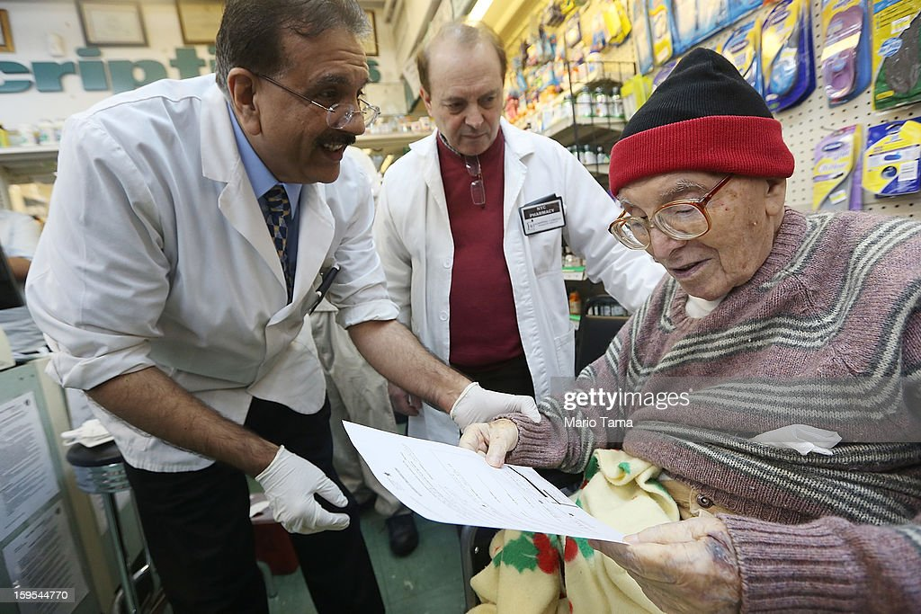 Chief pharmacist Ali A. Yasin (L) gives flu information to Juan Castro (R) after injecting him with influenza vaccine as assistant Agripinno Camiolo looks on at New York City Pharmacy in Manhattan on January 15, 2013 in New York City. The state of New York has declared a public health emergency in a flu epidemic of nearly 20,000 confirmed cases in the state.