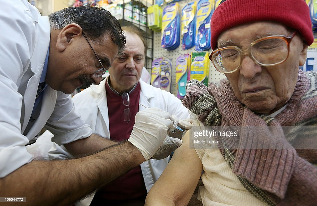 Chief pharmacist Ali A. Yasin (L) injects <a gi-track='captionPersonalityLinkClicked' href=/galleries/search?phrase=Juan+Castro&family=editorial&specificpeople=210684 ng-click='$event.stopPropagation()'>Juan Castro</a> (R) with influenza vaccine as assistant Agripinno Camiolo looks on at New York City Pharmacy in Manhattan on January 15, 2013 in New York City. The state of New York has declared a public health emergency in a flu epidemic of nearly 20,000 confirmed cases in the state.