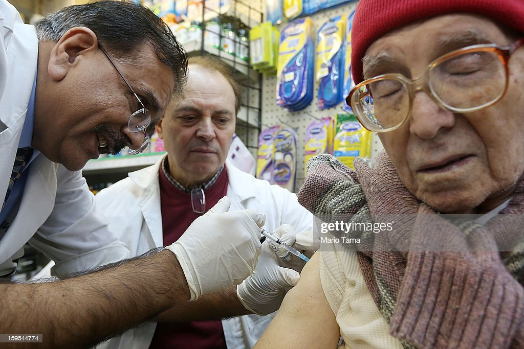 Chief pharmacist Ali A. Yasin (L) injects Juan Castro (R) with influenza vaccine as assistant Agripinno Camiolo looks on at New York City Pharmacy in Manhattan on January 15, 2013 in New York City. The state of New York has declared a public health emergency in a flu epidemic of nearly 20,000 confirmed cases in the state.