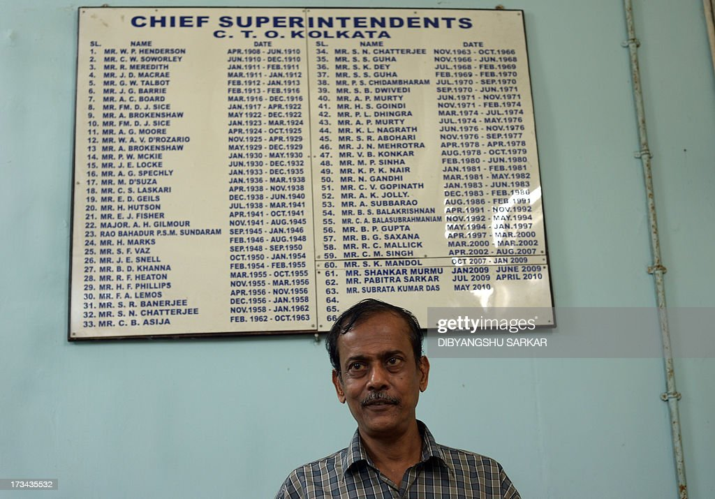 Chief Superintendent of Central Telegraph Office (CTO) Kolkata, Subrata Kumar Das looks on as he stands in front of a board with the names of all CTO Superintendents since April 1908, at the Central Telegraph Office in Kolkata on July 14, 2013. After 162 years of connecting people, India is now set to disband the world's last major telegram service and its legions of cycle-borne delivery workers - July 14 is the last day that messages will be accepted by the service, the world's last major commercial telegram operation. AFP PHOTO/Dibyangshu SARKAR
