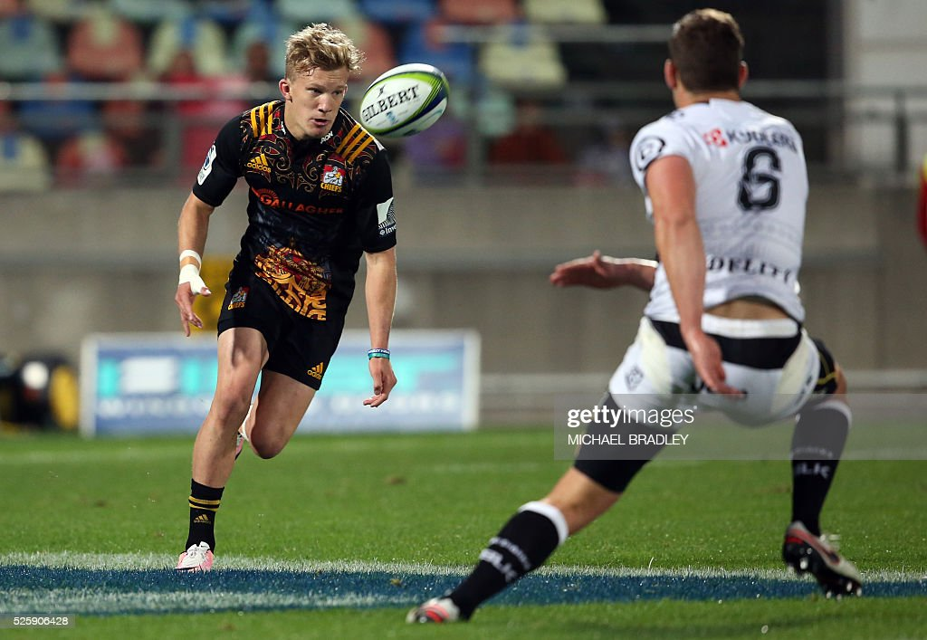 Chiefs' Damian McKenzie (L) chips the ball over Sharks' Keegan Daniel (R) during the Super Rugby match between the Waikato Chiefs of New Zealand and Coastal Sharks of South Africa at Yarrow Stadium in New Plymouth on April 29, 2016 / AFP / MICHAEL