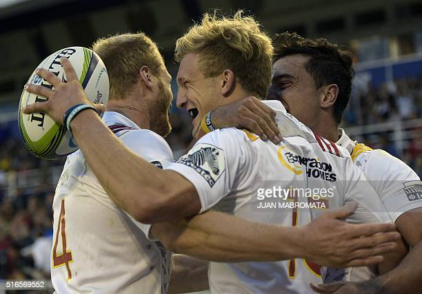 Chiefs' full back Damian McKenzie celebrates with teammates wing Sam McNicol and wing James Lowe after scoring a try against the Jaguares during...