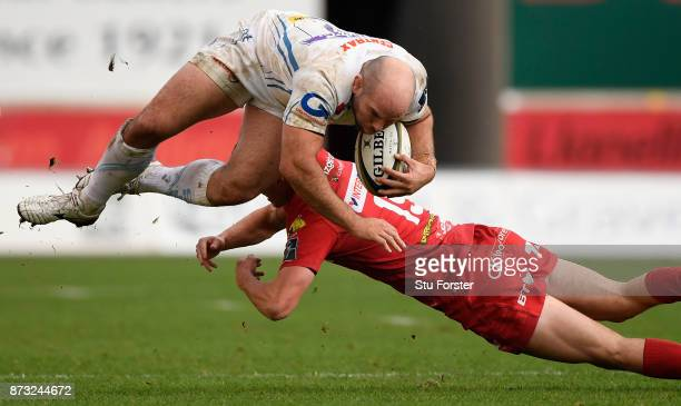 Chiefs hooker Shaun Malton goes over the tackle of Morgan Williams during the Anglo Welsh Cup match between Scarlets and Exeter Chiefs at Parc y...