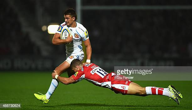 Chiefs player Henry Slade breaks the tackle of Gloucester centre Henry Purdey during the Aviva Premiership match between Gloucester Rugby and Exeter...
