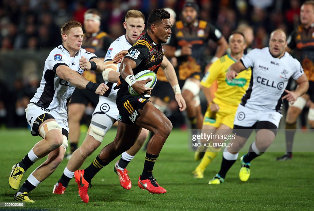 Chiefs' Seta Tamanivalu (C) breaks the tackle to score a try during the Super Rugby match between the Waikato Chiefs of New Zealand and Coastal Sharks of South Africa at Yarrow Stadium in New Plymouth on April 29, 2016 / AFP / MICHAEL