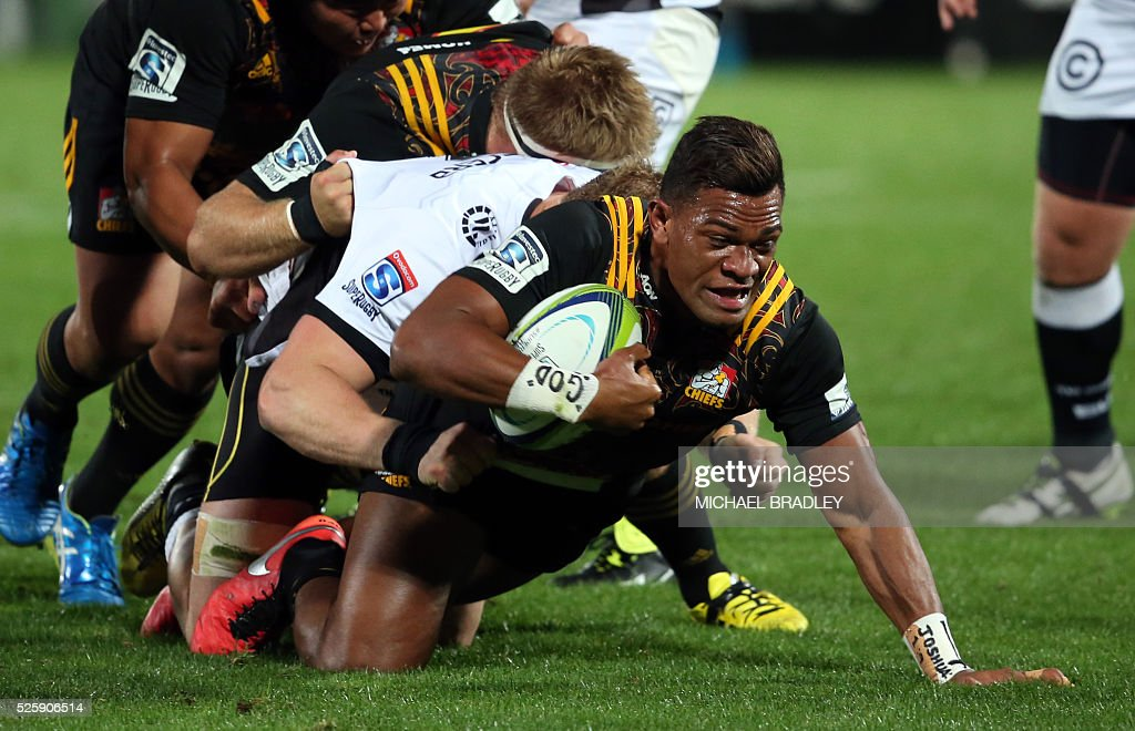Chiefs' Seta Tamanivalu (C) is tackled by the Sharks' Jean-Luc du Preez (white) during the Super Rugby match between the Waikato Chiefs of New Zealand and Coastal Sharks of South Africa at Yarrow Stadium in New Plymouth on April 29, 2016 / AFP / MICHAEL