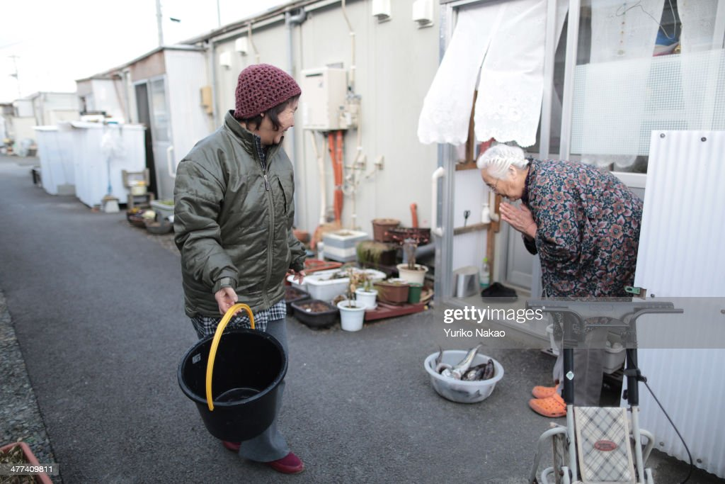 Chieko Miura (L) is thanked by her neighbor after giving fish to her outside their temporary houses on March 9, 2014 in Otsuchi, Iwate, Japan. On March 11 Japan commemorates the third anniversary of the magnitude 9.0 earthquake and tsunami that claimed more than 18,000 lives, and subsequent nuclear disaster at the Fukushima Daiichi Nuclear Power Plant.