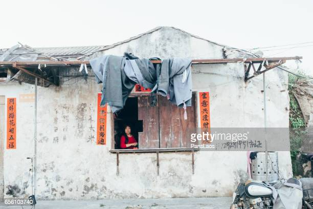 Chiense woman opening a window of traditional department store