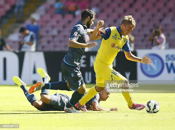 Chievo's Argentinian forward Maxi Lopez fights for the ball with Napoli's Spanish defender Raul Albiol and Napoli's Swiss midfielder Gokhan Inler...