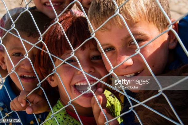 TOPSHOT Chiildren smile and look through a fence at a UNHCR refugee camp in Hammam alAlil on the outskirts of Mosul on July 12 2017 / AFP PHOTO /...