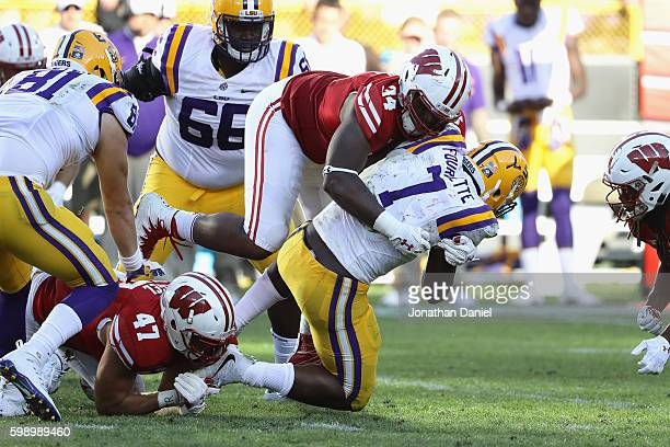 Chikwe Obasih of the Wisconsin Badgers tackles Leonard Fournette of the LSU Tigers during the second half at Lambeau Field on September 3 2016 in...
