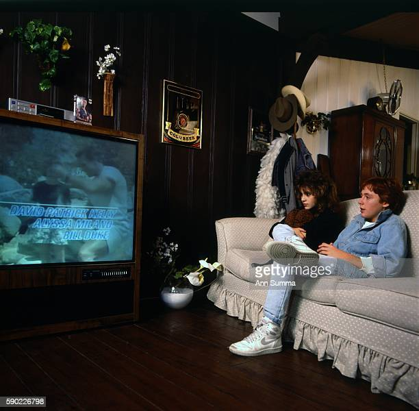 Child actors Alyssa Milano with Scott Grimes interacting watching their film 'Commando' at her home in LA 1/28/1986
