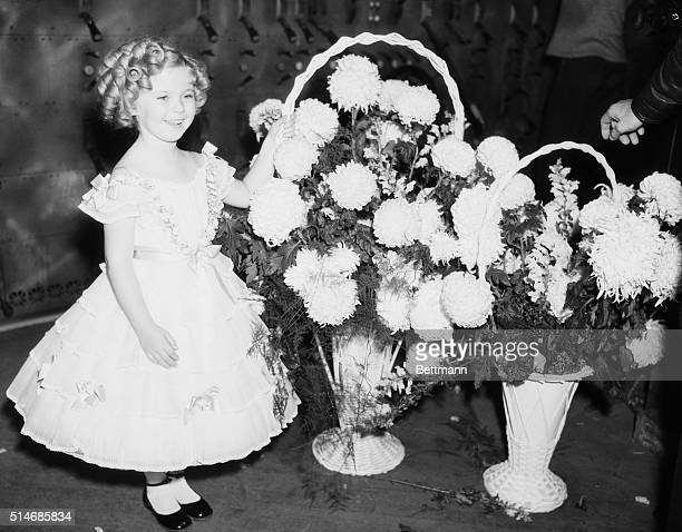 Child actress Shirley Temple stands with baskets of flowers on December 3 1935 She is backstage during the Will Rogers Memorial 'Show of Shows' This...