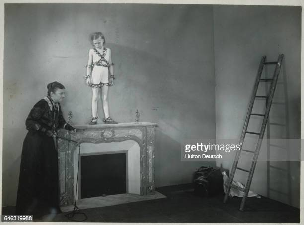 A child actress stands on a fireplace mantel as another actress holding a rope approaches in a performance of Jean Cocteau's experimental theatre