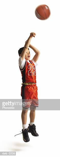 child african american male basketball player in a red uniform and untied shoe jumps and shoots