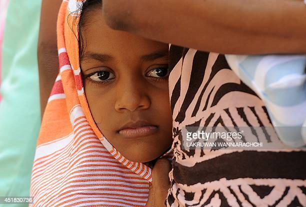 A child amongst a group of Sri Lankan asylum seekers sent back by Australia looks on before entering the magistrate's court in the southern port...