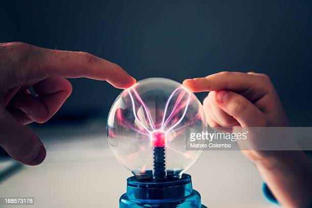 Child and adult fingers touching a plasma ball