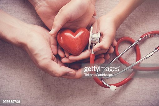 child and adult holding red heart with stethoscope, heart health,  health insurance concept : Stock Photo