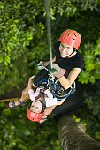 Child and an adult suspended on a rope in the forest