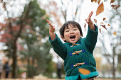 A child is in the beautiful autumn leaves field in Tokyo, Japan, photographed naturally without heavy processing.