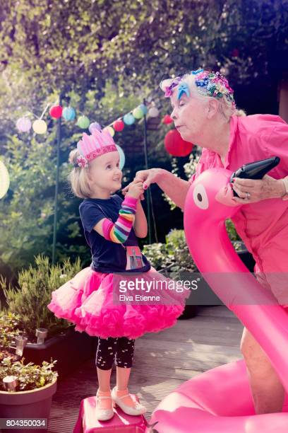 Child and grandmother playing dress-up in offbeat and colorful scene