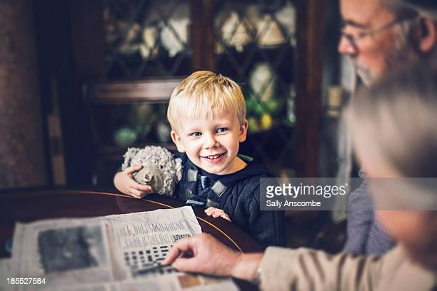 Child and Grandparents looking at a newspaper