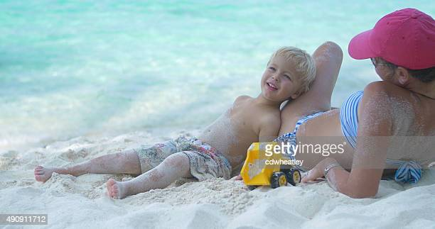 child and his mother relaxing on a tropical beach